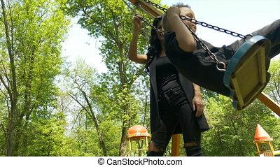Babysitter pushing baby boy on swing set and enjoying a...