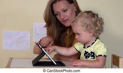 Babysitter teaching little child girl using tablet computer....