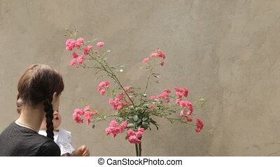 Babysitter with baby girl with rosebush in the yard