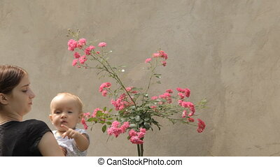 Babysitter with baby with rosebush in the yard