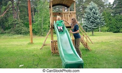 Babysitter woman help toddler child to slide down in playground.