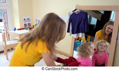 babysitter woman playing with toddler girl near mirror....