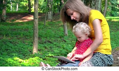 Babysitter woman with cute baby girl using tablet computer in park