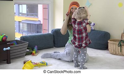 Babysitter woman with toddler girl measure hat at work.