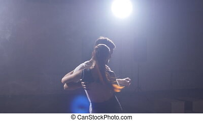 Bachata Dancers performing in the dark lighted room -...