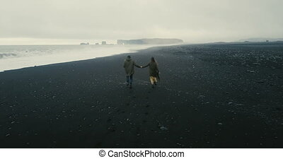 Back aerial view of the young couple running on the black volcanic beach in Iceland. Romantic date near the sea.