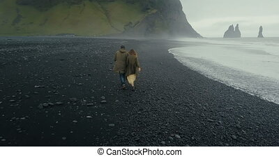 Back aerial view of the young hipster couple running on the black volcanic beach near the troll toes in Iceland.