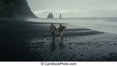 Back aerial view of young hipster couple running on the black volcanic beach near the troll toes in Iceland.