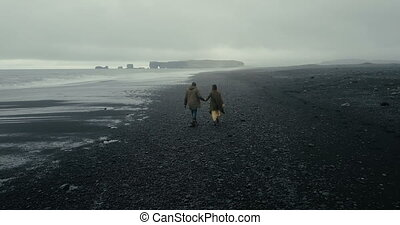 Back aerial view of young hipster couple walking on the black volcanic beach in Iceland. Man and woman enjoy the sea.