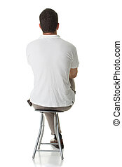 An adult man sitting on a stool, with his back facing the camera.