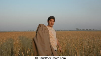 Back, an adult man walks the wheat field. Successful farmer...