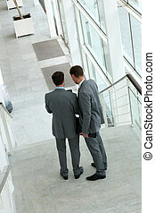 Back and upper view of business people standing in stairs