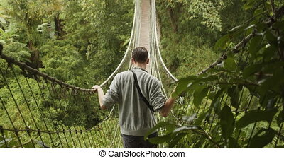 Back close up view of a man making his way across an unstable rope jungle bridge in the rain. Young man crossing a hanging bridge in Bali, Indonesia 4K