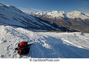 Wide angle view of a pair of back country ski and backpack on the top of the mountain in a clear bright day and scenic winter background.