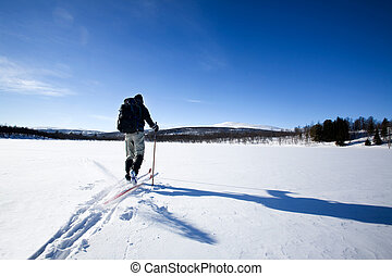 Back Country Skiing - A cross country skiier skiing off...