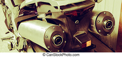 Back exhaust pipe of sportbike close-up in garage