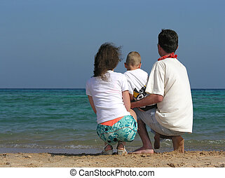 back family of three sit on beach