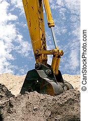 Back Hoe - A back hoe digging in piles of dirt.