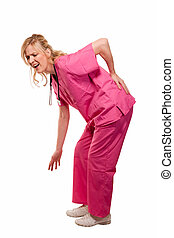 Blond lady nurse healthcare worker wearing pink scrubs standing bent over with hand on lower back with pained expression