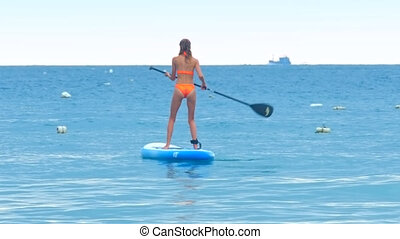 back lady paddles board in ocean against boat on horizon