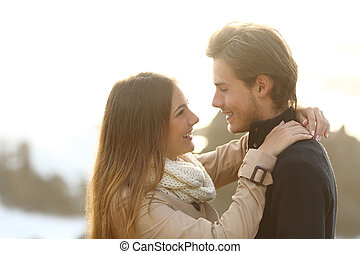 Back light of a couple ready to kiss looking each other isolated on white above