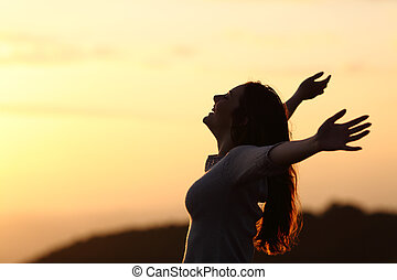 Back light of a woman breathing raising arms with a warm...