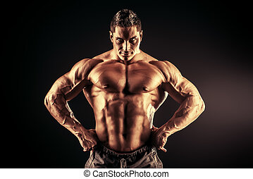 back light - Handsome muscular bodybuilder posing over black...
