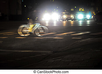 Back lit cyclist in blurred motion at night