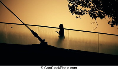 Back Lit Silhouette of Young Woman Holding Mobile Phone...