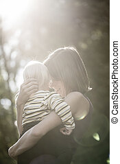 Back lit woman holding small child