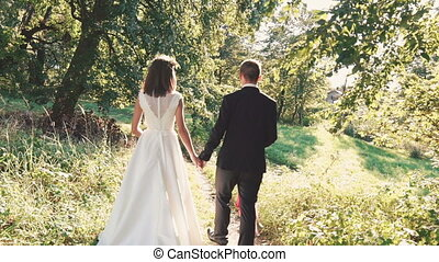 Back look of happy married couple walk together in the park. Slowly
