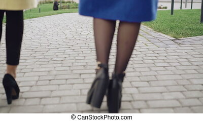 Back look of legs of two girls in coats walking on the pavement 4K