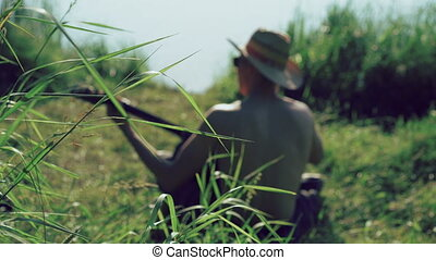 Back look of young boy in sunglasses and hat playing the guitar near lake. 4k