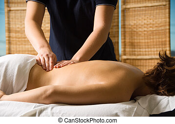 Back massage - woman in a day spa getting a good massage