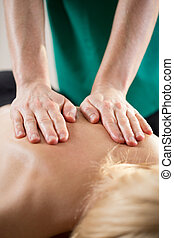 Back mobilization - Close-up of experienced physiotherapist...