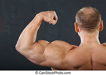 Back, neck and hand muscles of undressed tanned wet bodybuilder