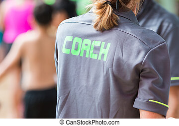 back of a coach's grey shirt with the green word Coach written on it