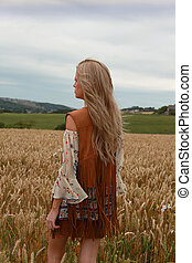 Back of a girl standing in a meadow