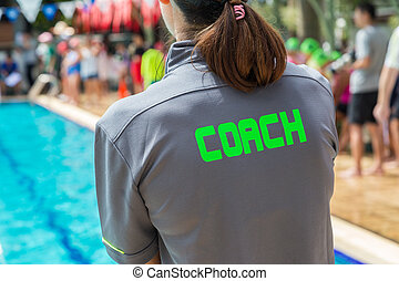 back of a swim coach's grey shirt with the green word Coach written on it