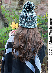 Back of a womans head wearing a pom pom hat and holding a autumnal leaf