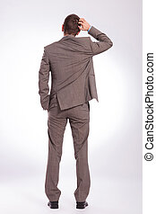 back of a young business man scratching his head