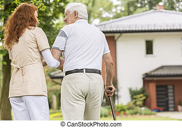 Back of an elderly man with a cane and his caregiver outside in the garden walking back to the care home.