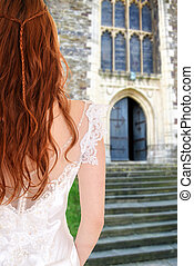 bride outside church by stone stairs