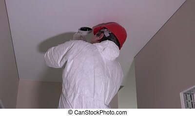 Back of constructor man with helmet cutting hole in ceiling