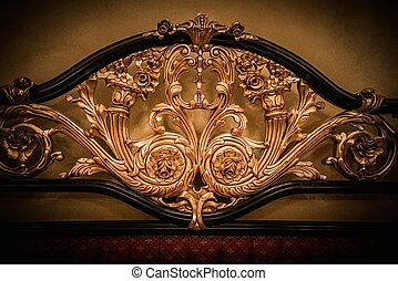 Back of expensive bed with golden ornament