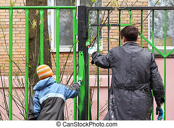 Back of little boy and his father, they dye fence by green color on community work day