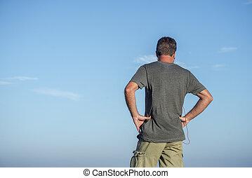 Back of man against sky