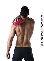 Back of muscular man with shoulder pain, holding hot water bottle