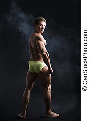 Back of muscular young bodybuilder in relaxed pose, smiling