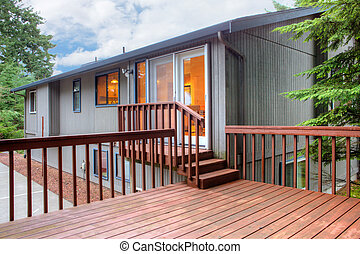 Back of the brown house with simple deck.